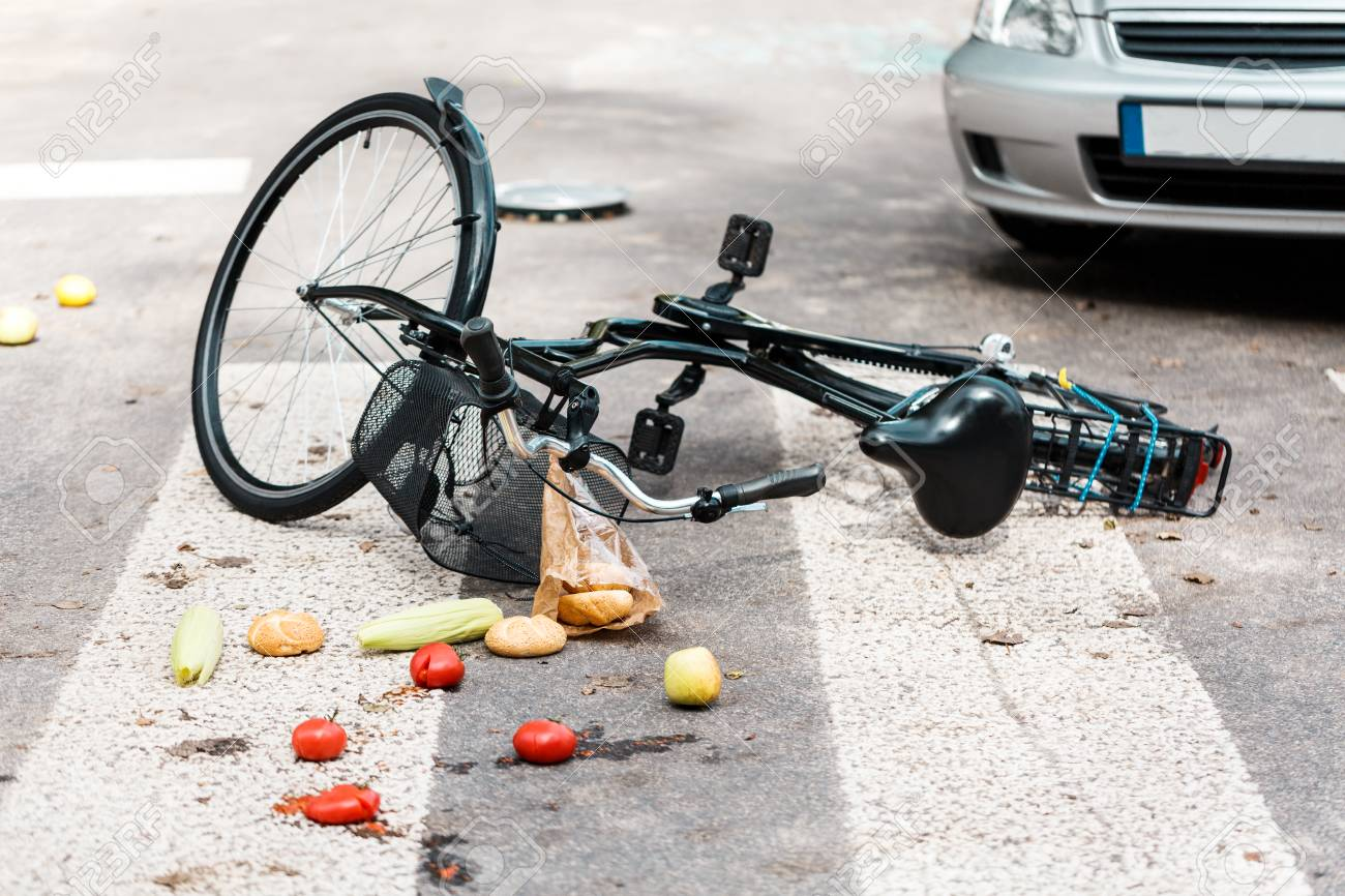 97415385-fresh-vegetables-and-bread-rolls-scattered-on-the-road-after-an-accident-with-bike-hit-by-a-car-on-p.jpg